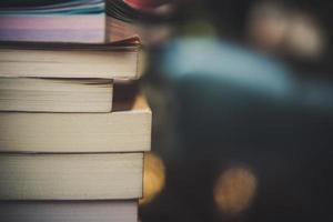pilhas de livros em uma mesa sobre um fundo desfocado de biblioteca