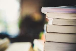 pilhas de livros em uma mesa sobre um fundo desfocado de biblioteca foto