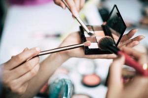 mulheres fazendo maquiagem com pincéis e pó cosmético