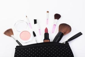 vista de cima de uma bolsa de maquiagem com produtos de beleza