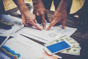 grupo de empresários analisa gráficos em reunião foto