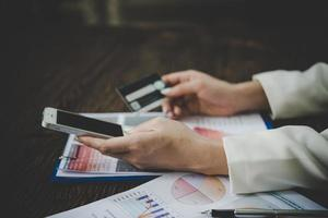 mulher usando cartão de crédito e telefone inteligente para fazer compras online foto
