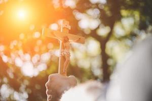 mãos segurando uma cruz de madeira sobre o céu foto