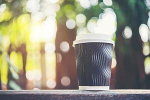 xícara de café de papel em fundo natural de manhã foto