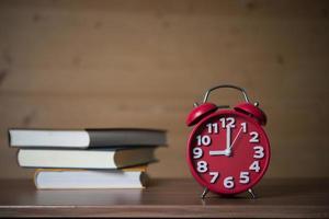 despertador às 9h e pilha de livros com café