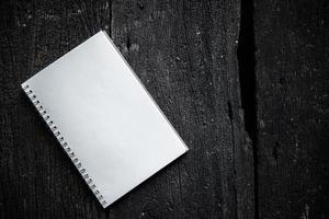 caderno em fundo de textura de madeira foto