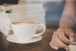 mãos de mulher relaxando com café no café foto