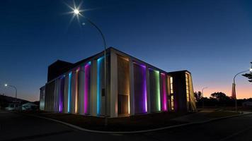 edifício iluminado de verde roxo e amarelo durante a noite
