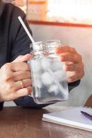 pessoa segurando uma jarra de vidro com água