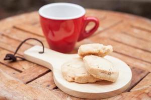 xícara de café vermelha e biscoitos