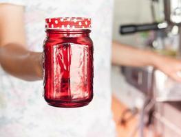 barista segurando uma jarra vermelha foto