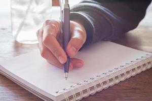mão escrevendo com uma caneta roxa foto