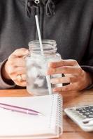 mãos segurando um copo de água fria