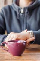 xícara de café roxa em uma mesa na frente de uma pessoa