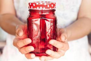pessoa segurando uma jarra vermelha