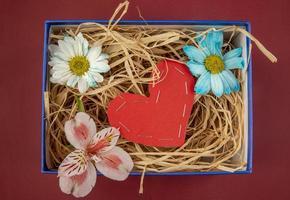 vista superior de uma caixa de flores e um coração de feltro vermelho