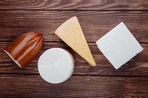 vista superior de diferentes tipos de queijos em fundo de madeira rústico foto