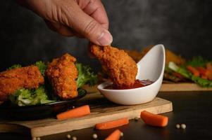 mão mergulhando frango frito crocante no molho foto