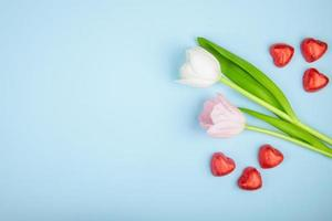 tulipas e chocolates em forma de coração em um fundo azul foto