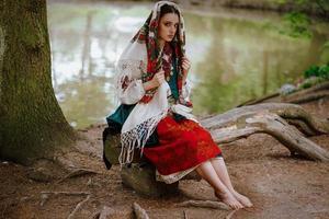 menina ucraniana sentada perto do lago foto