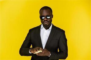 homem de óculos escuros segurando dinheiro foto