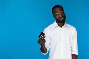 homem de camisa branca segurando um cartão de crédito