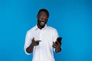 um homem sorridente olhando para o telefone