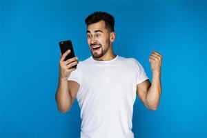homem animado olhando para seu telefone inteligente foto
