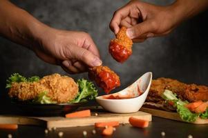 duas mãos segurando rodelas de frango crocante em molho de tomate foto