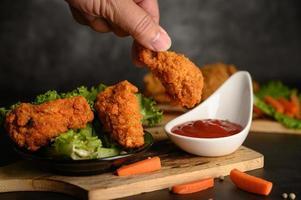 Mão mergulhando frango frito crocante foto