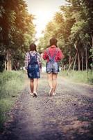 duas meninas caminhando ao longo de uma estrada na floresta na natureza