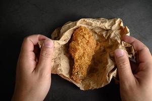 mãos pegando frango frito crocante em papel pardo