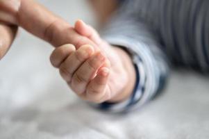 a mão do bebê recém-nascido segura os dedos da mãe