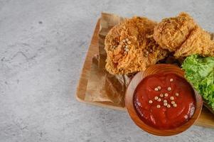 frango frito crocante em uma tábua com molho de tomate, vista de cima foto