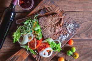 Bife grelhado com vegetais em uma tábua de madeira foto