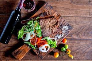 bife e salada em uma tábua de madeira