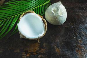 cocos e uma folha de palmeira em um fundo de madeira foto