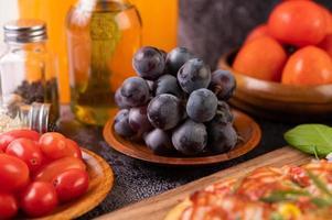 uvas pretas com tomate suco de laranja e pizza foto