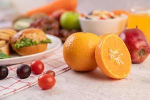 laranjas cortadas ao meio com maçãs, uvas e hambúrgueres