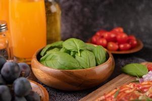tomilho e tomate em um copo de madeira com alho foto