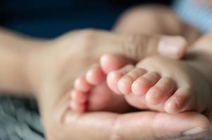 mãos de mães segurando pés de bebê foto