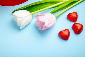 tulipas e doces em forma de coração em um fundo azul foto