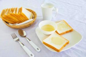pão e leite condensado doce na mesa foto