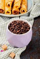 grãos de café em uma xícara rosa