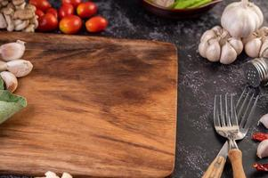 alho, tomate e uma tábua de cortar foto