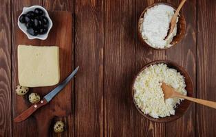 vista superior do queijo em tigelas e em uma tábua de cortar foto