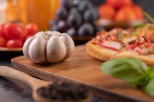 Alho, manjericão e sementes de pimenta em close-up em uma tábua foto