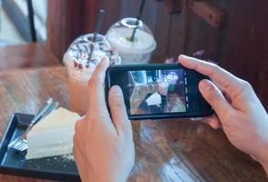 pessoa tirando uma foto de bolo e café