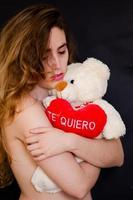 garota segurando um bicho de pelúcia que diz te quiero foto