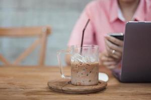café gelado em uma cafeteria com uma mulher trabalhando